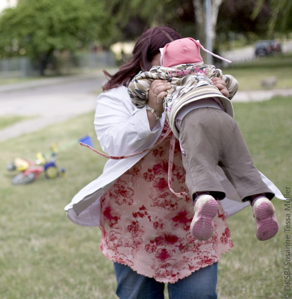 Babysitter 25+ mit Baby auf dem Arm