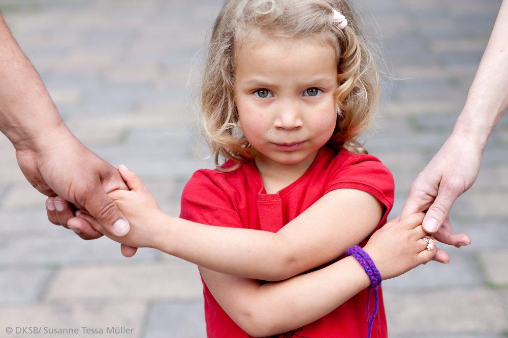 kleines Mädchen hält zwei Hände fest