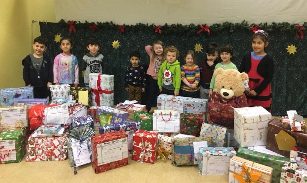 Zehn lächende Kinder mit ganz vielen Geschenken