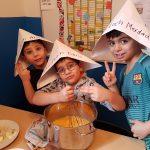 Drei Kinder beim kochen mit Papierhüten