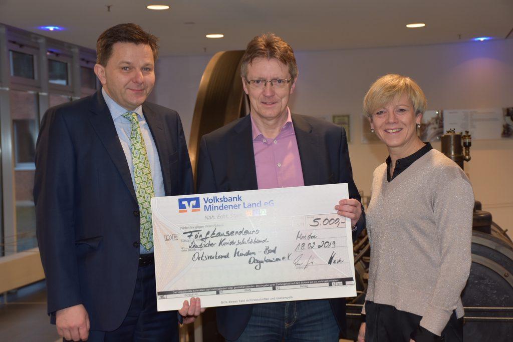 Drei Personen mit einem Spenden-Scheck über 5000 Euro