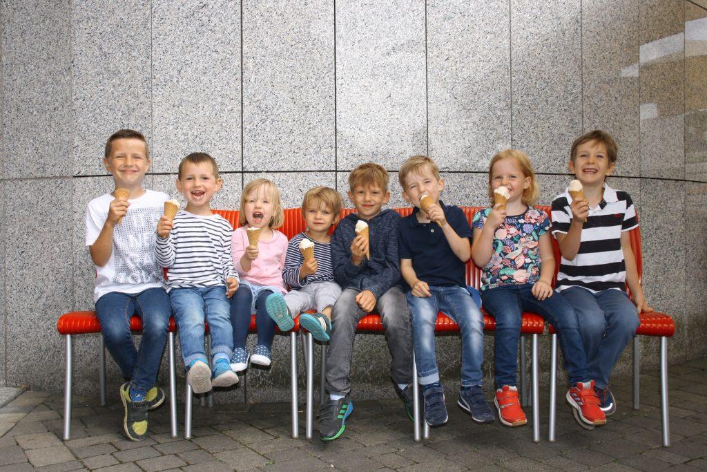 8 lachende Kinder auf Stühlen mit Eis in der Hand