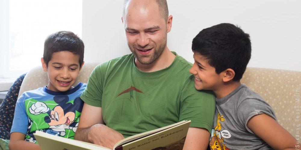Mann liest zwei Jungen ein Buch vor